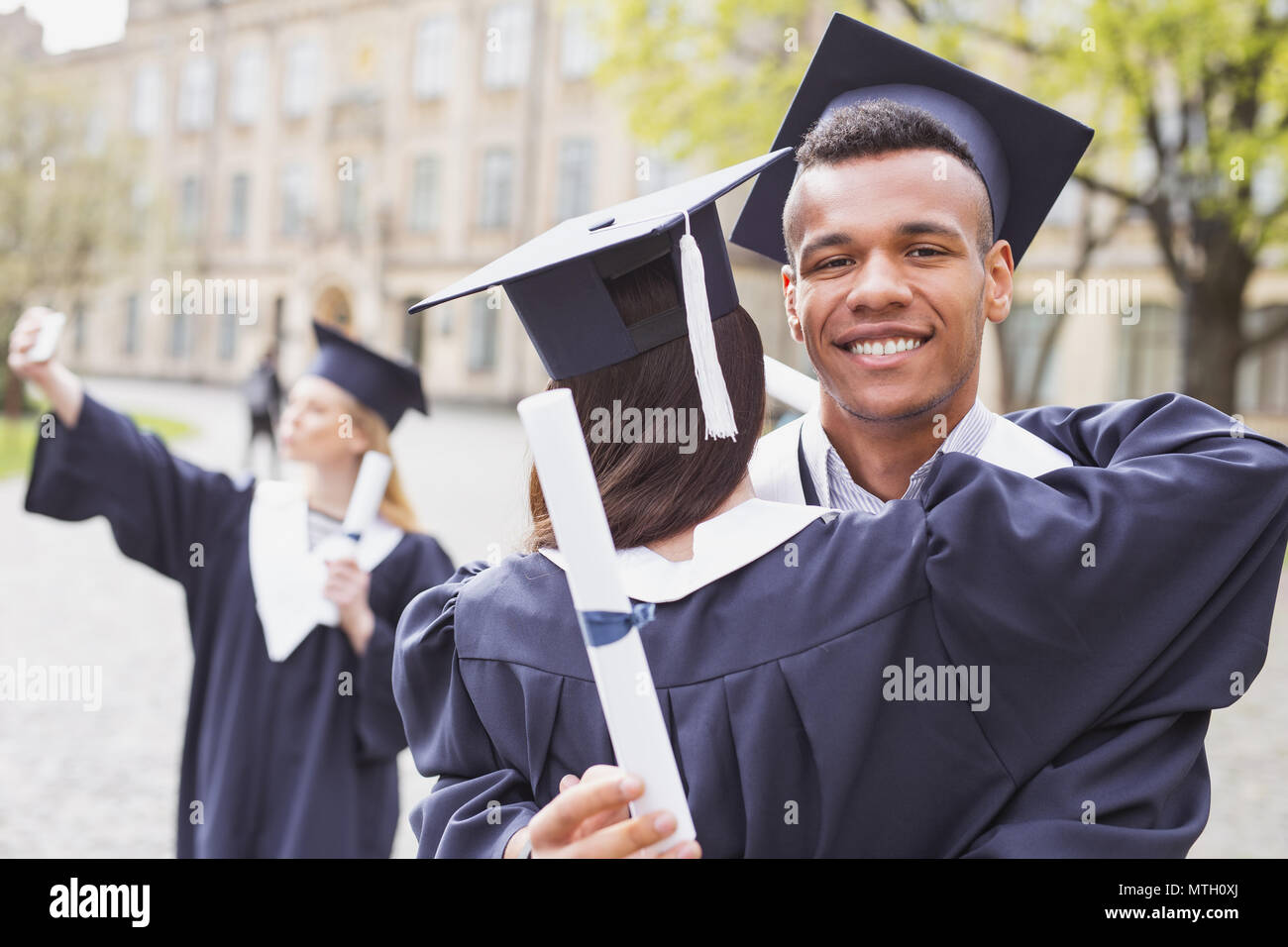 Smiling handsome graduate feeling happy after receiving diploma - Stock Image