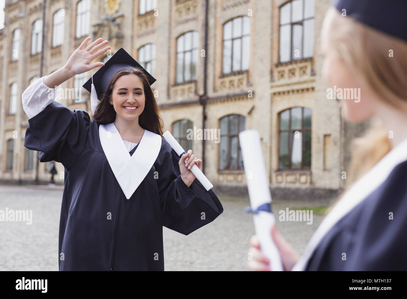 Smiling dark-haired graduate saying bye to her friends - Stock Image