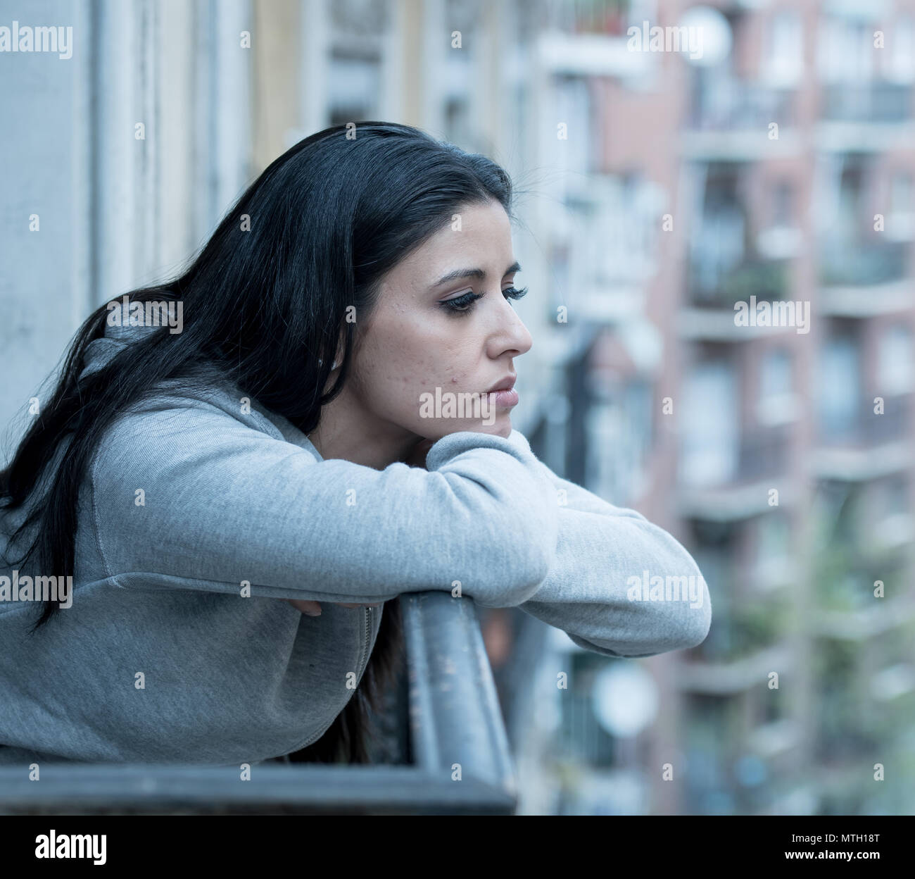Beautiful latin depressed lonely woman staring out feeling sad, pain and worried on a balcony at home. Crisis, depression and mental health concept - Stock Image