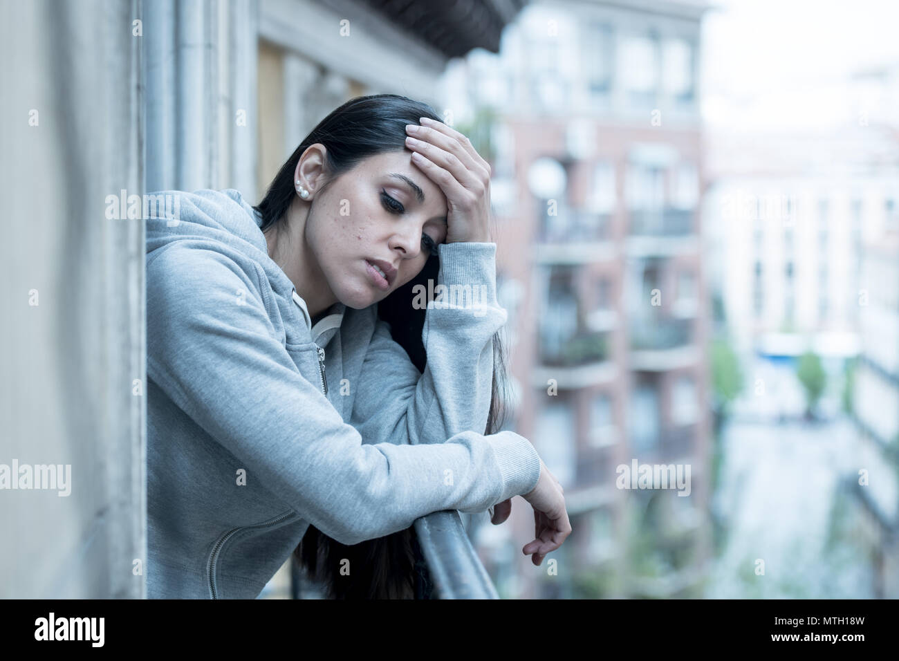Beautiful latin depressed lonely woman staring out feeling sad, pain, grief on a balcony at home. Crisis, depression and mental health concept - Stock Image