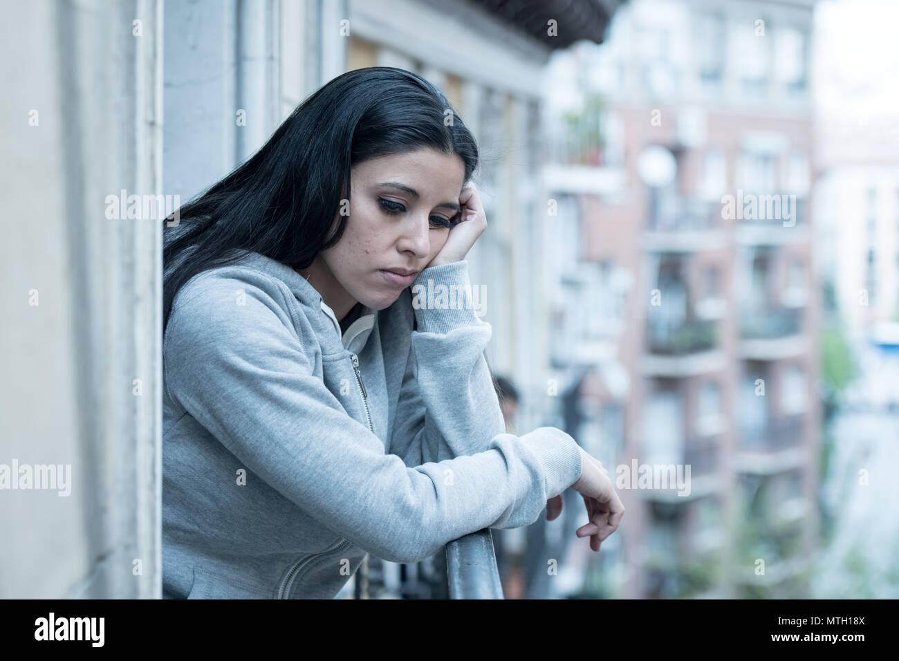 Attractive latin depressed lonely woman staring out feeling sad, pain, grief on a balcony at home. Crisis, depression and mental health concept - Stock Image