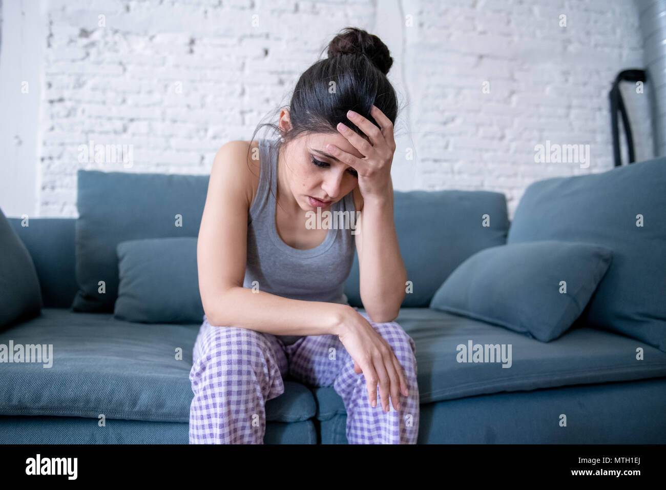 Beautiful latin depressed lonely woman staring out feeling sad, pain, grief at home on her sofa. Crisis, depression and mental health concept - Stock Image