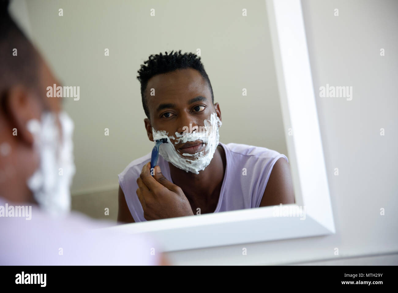Man shaving in the mirror Stock Photo