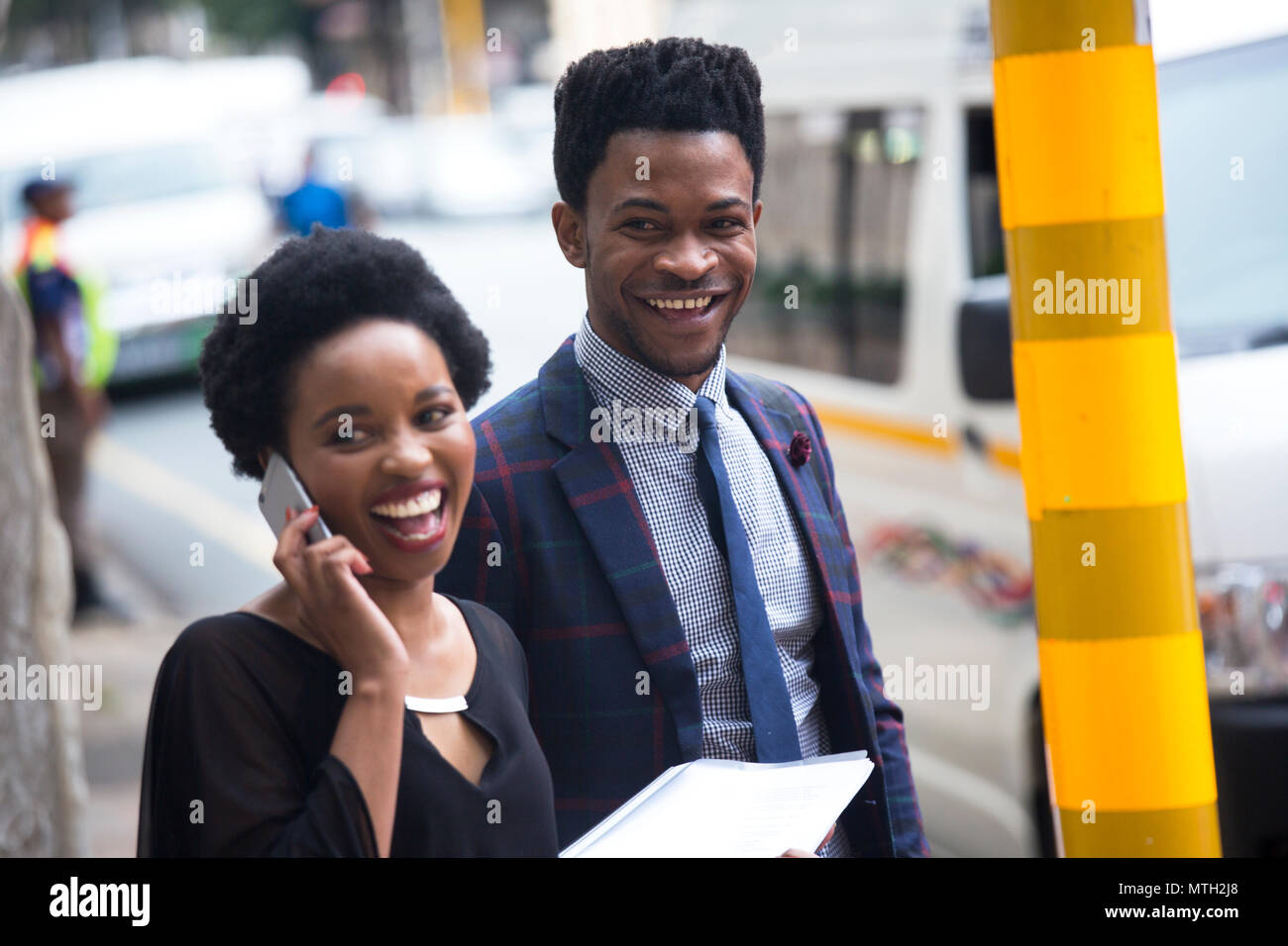 Business man and woman waiting at traffic light - Stock Image