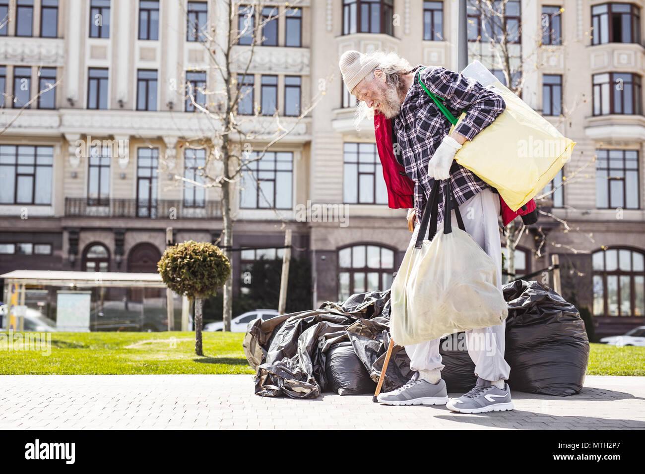 Sad poor man walking near the garbage bags - Stock Image