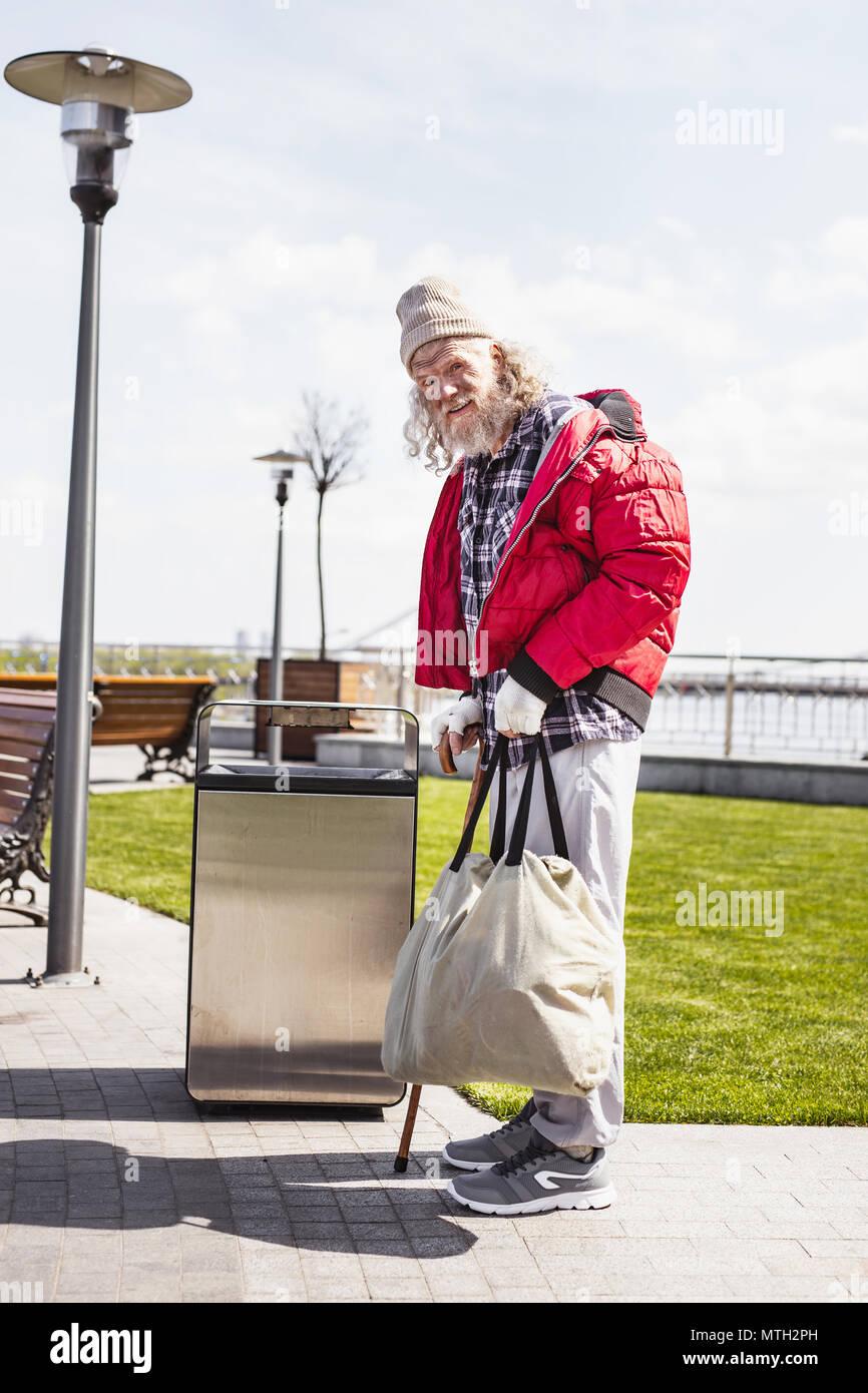 Serious poor man standing near the litter bin - Stock Image