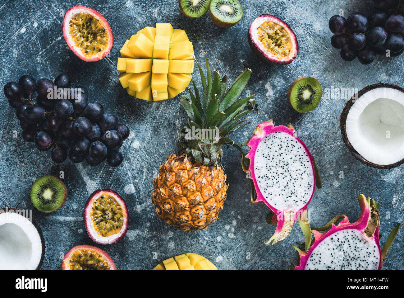 Tropical fruits, exotic fruits on concrete background. Fruit flat lay. Dragonfruit, passionfruit, coconut, mango, kiwi and grapes. Fresh raw fruit bac - Stock Image