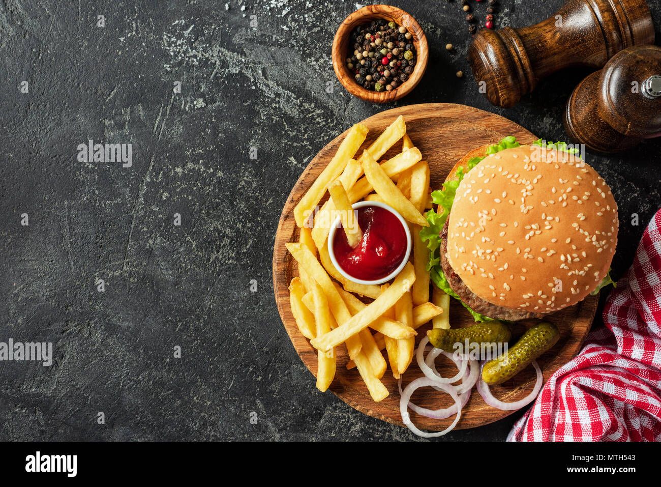 Burger and fries on wooden board on dark stone background. Homemade burger or cheeseburger, french fries and ketchup. Tasty sandwich. Top view with co - Stock Image