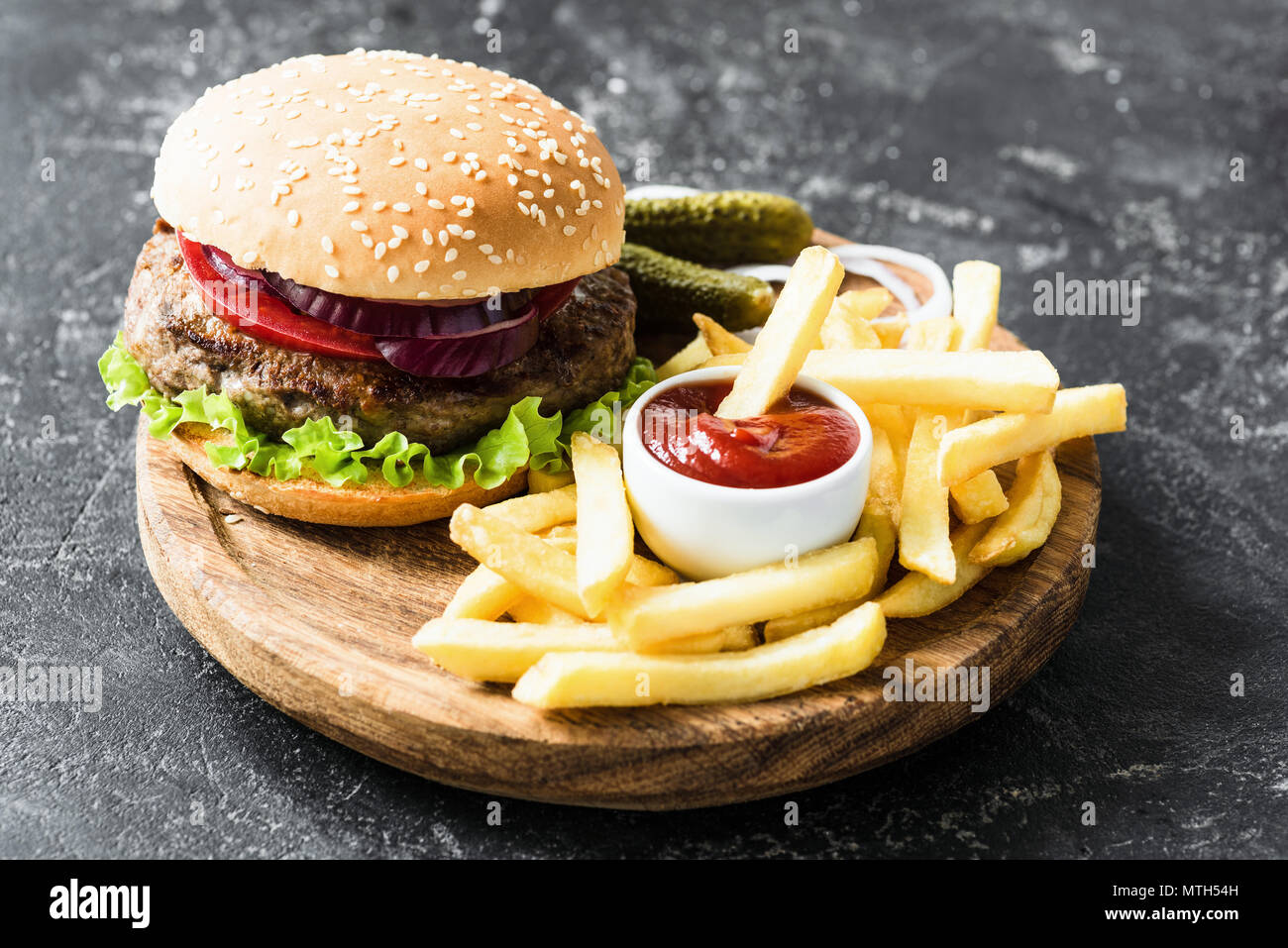 Beef burger with lettuce and tomato, potato fries and ketchup. Fast food - Stock Image