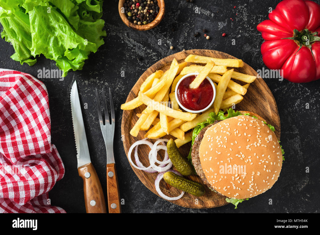 Beef burger with lettuce and tomato, potato fries and ketchup on dark background. Table top view. Fast food, unhealthy eating concept - Stock Image