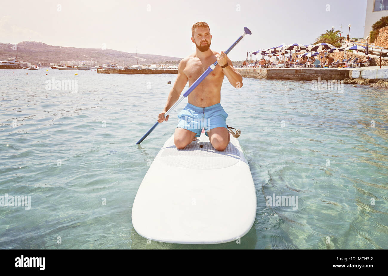 Adult bearded man beginner surfer kneel on paddle board on sea. Summer active vacation and water sport concept - Stock Image