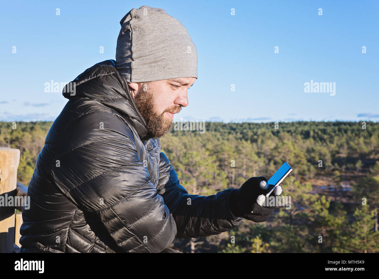 Caucasian bearded man looking at smartphone against blue sky and forest outdoor lifestyle and smartphone addiction concept - Stock Image
