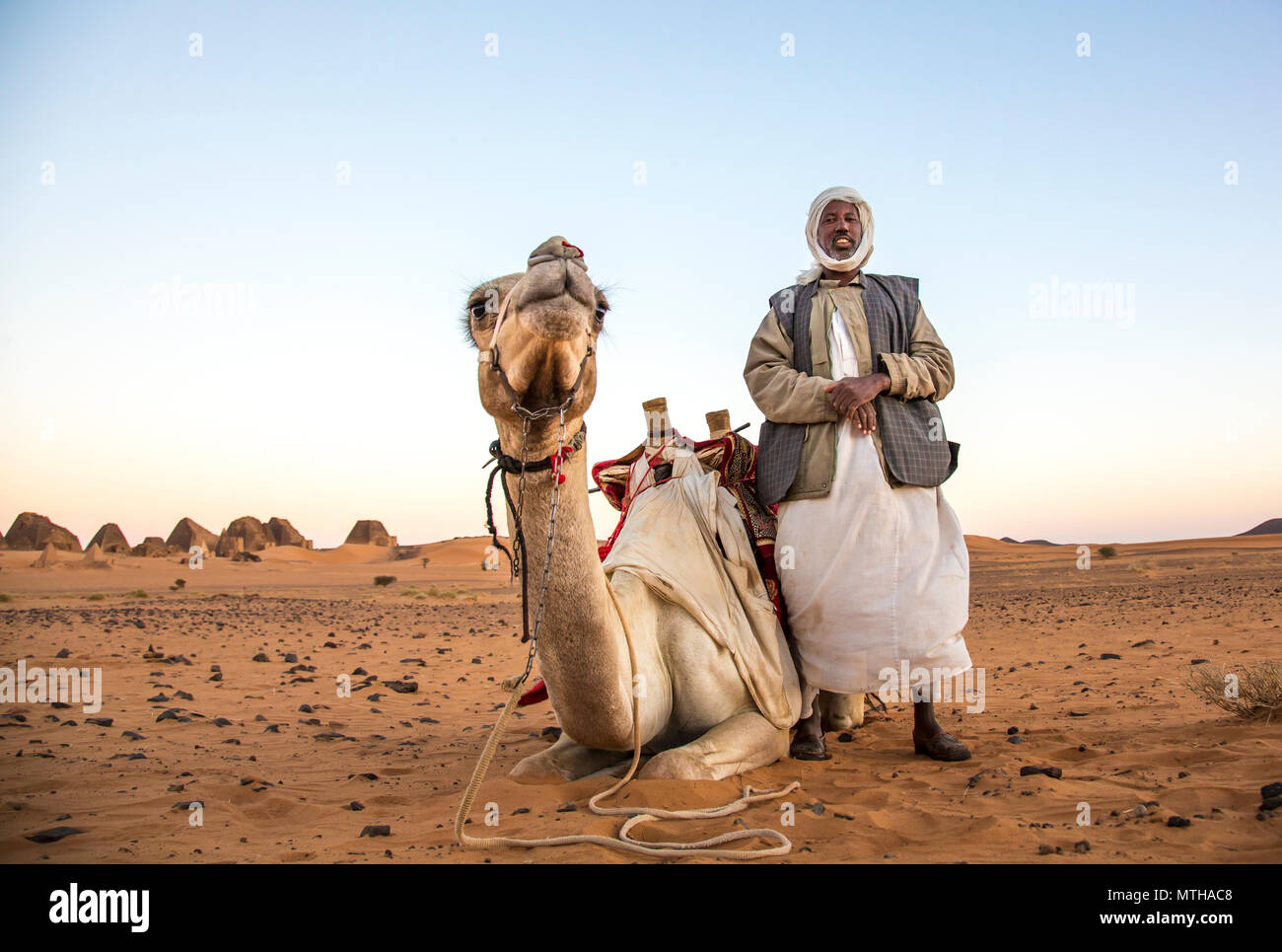 Meroe Pyramids, Sudan- 19th December, 2015: a man with his camel in a desert - Stock Image