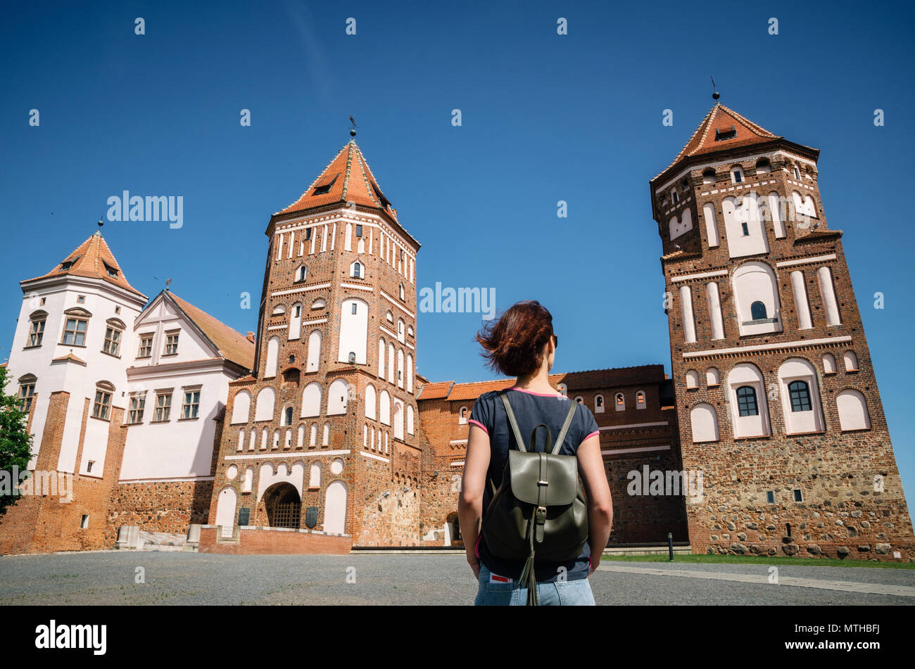 Young woman traveler with backpack looks at Medieval castle in Mir, Belarus - Stock Image