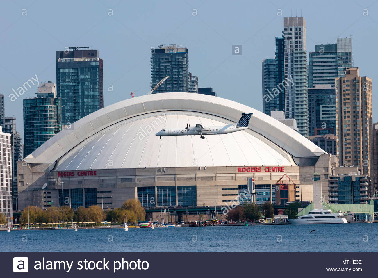 Porter Airlines Bombardier Dash 8 Q400 landing at City Centre Airport passing the Rogers Centre downtown Toronto Ontario Canada - Stock Image
