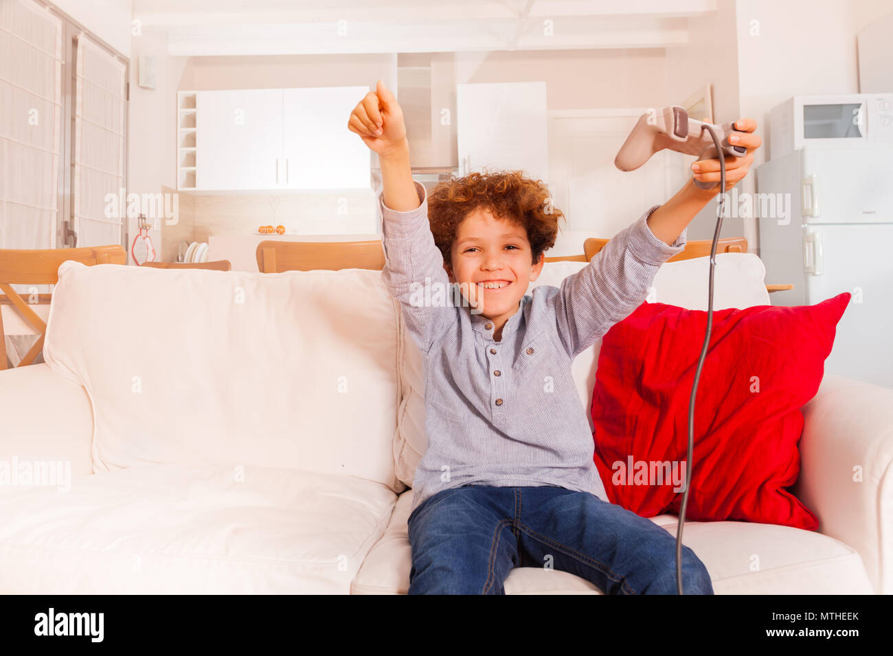 Portrait of joyful preteen boy with joystick playing videogames at home - Stock Image