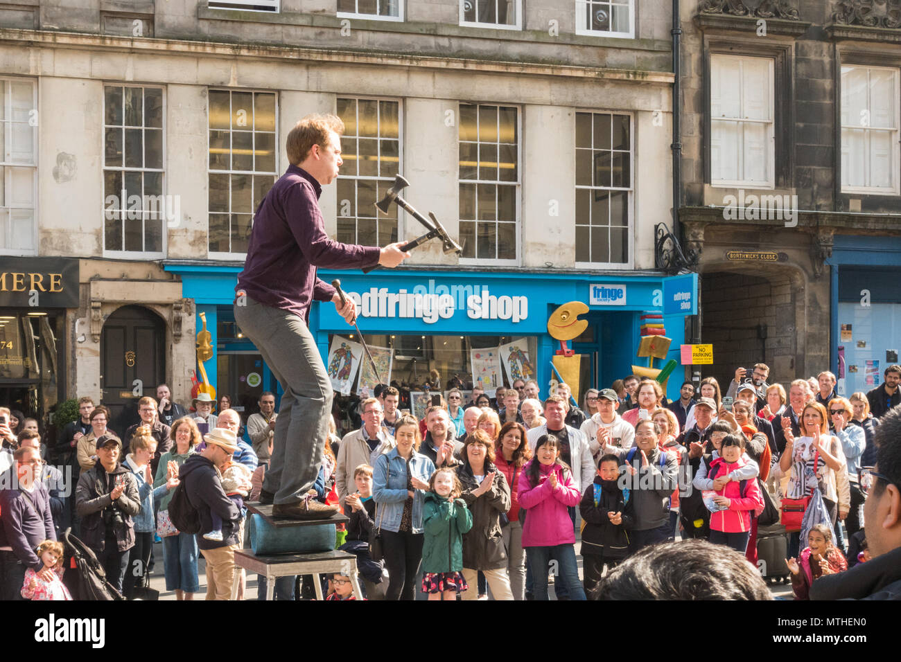 male Street performer juggling a knife and axes while balancing in front of large crowd on Edinburgh's Royal Mile, Scotland, UK - Stock Image