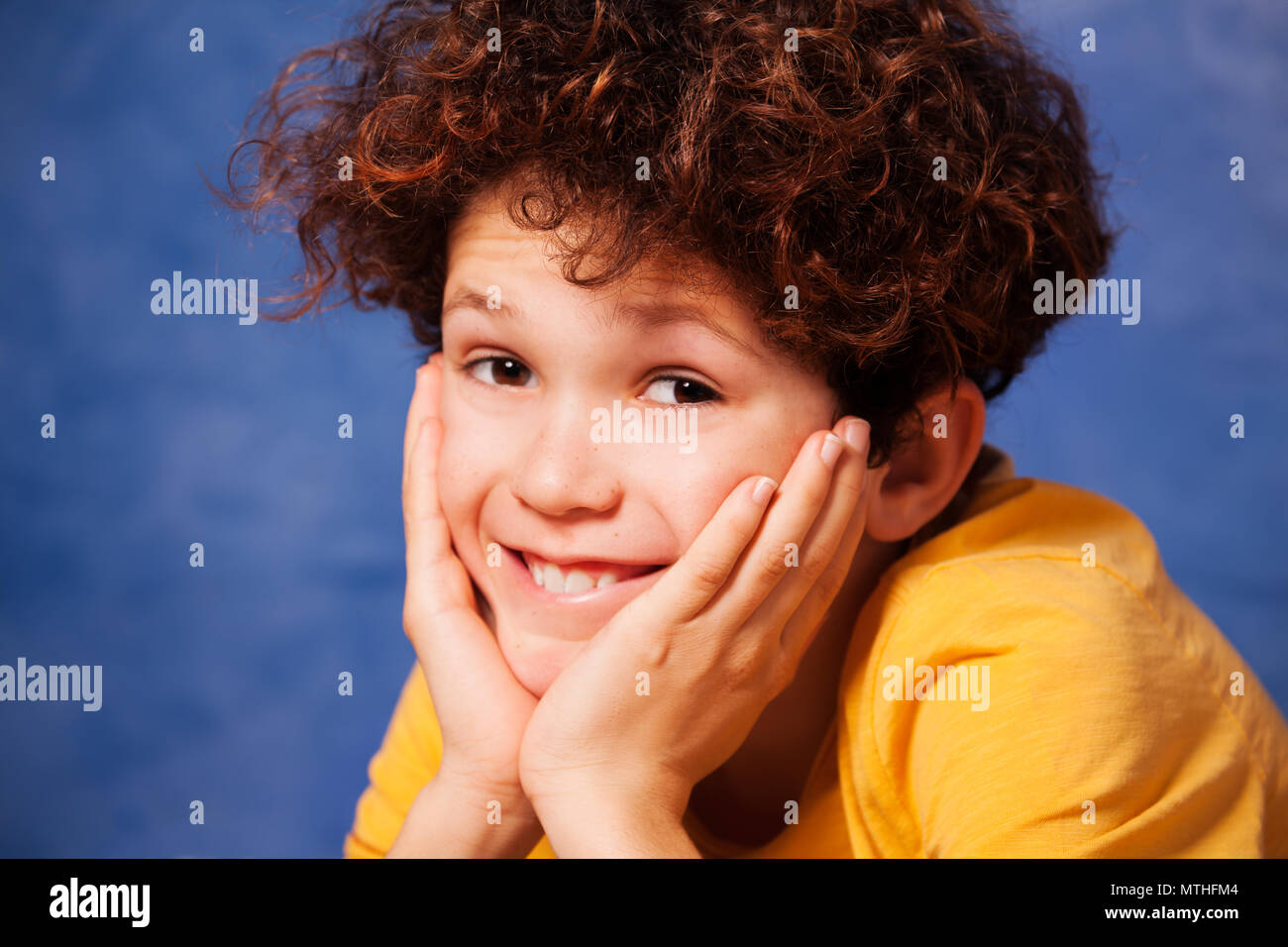 Happy preteen boy with curly hair resting chin on hands and looking at camera - Stock Image