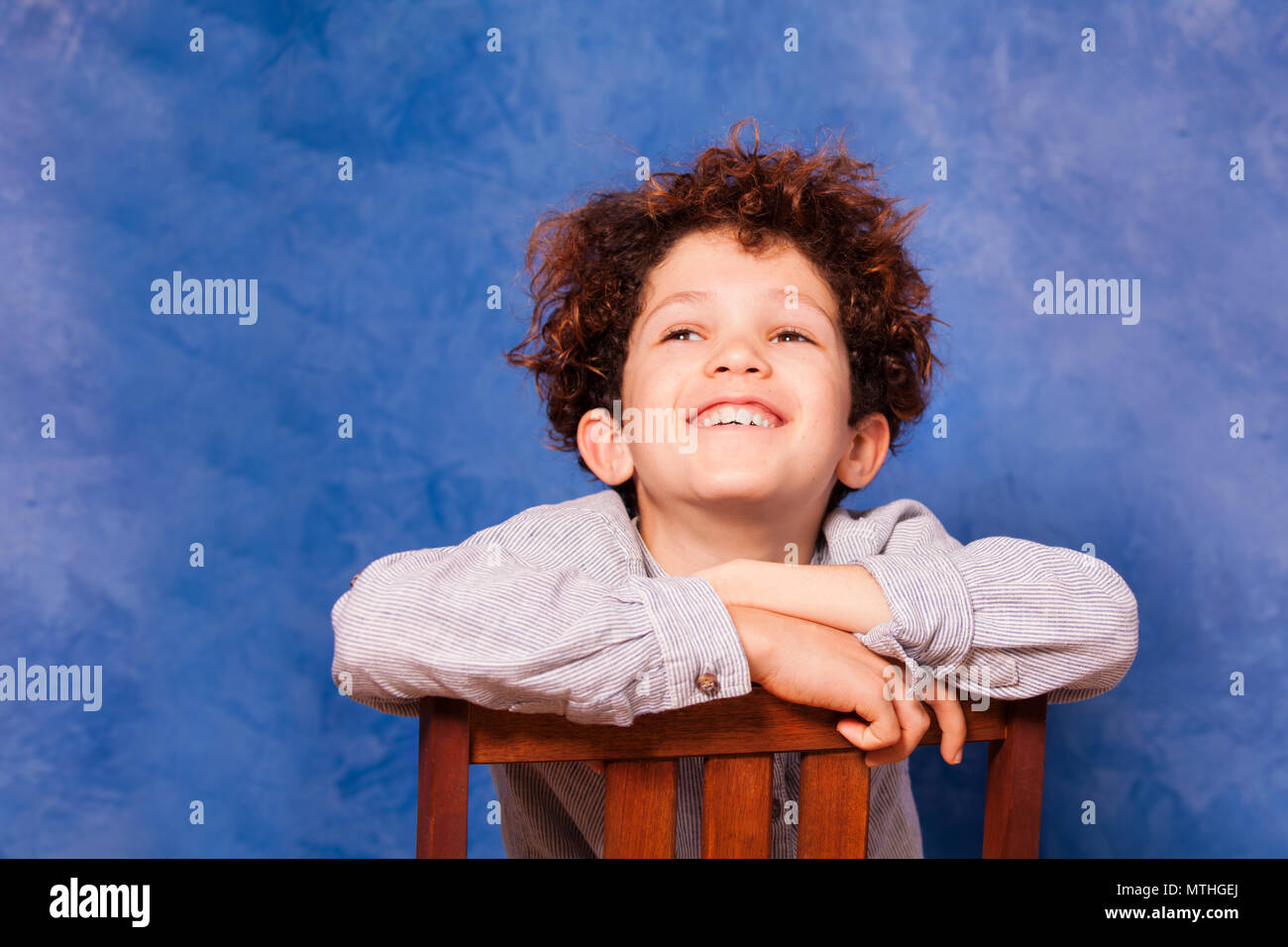 Happy preteen boy with curly hair looking upward while sitting backwards on wooden chair against blue background - Stock Image