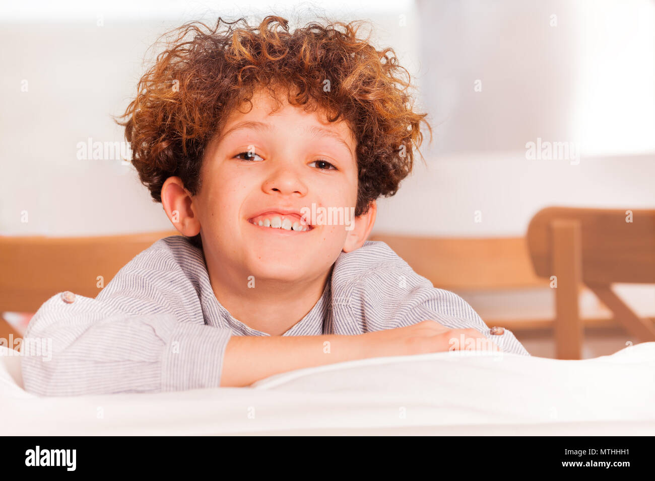Portrait of happy preteen boy sitting backwards on white sofa in the lounge room - Stock Image