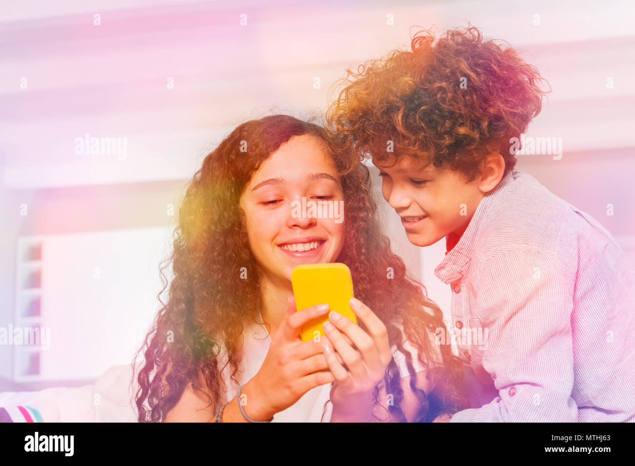 Indoor shot of teenage boy and girl using yellow mobile phone, texting in social networks - Stock Image