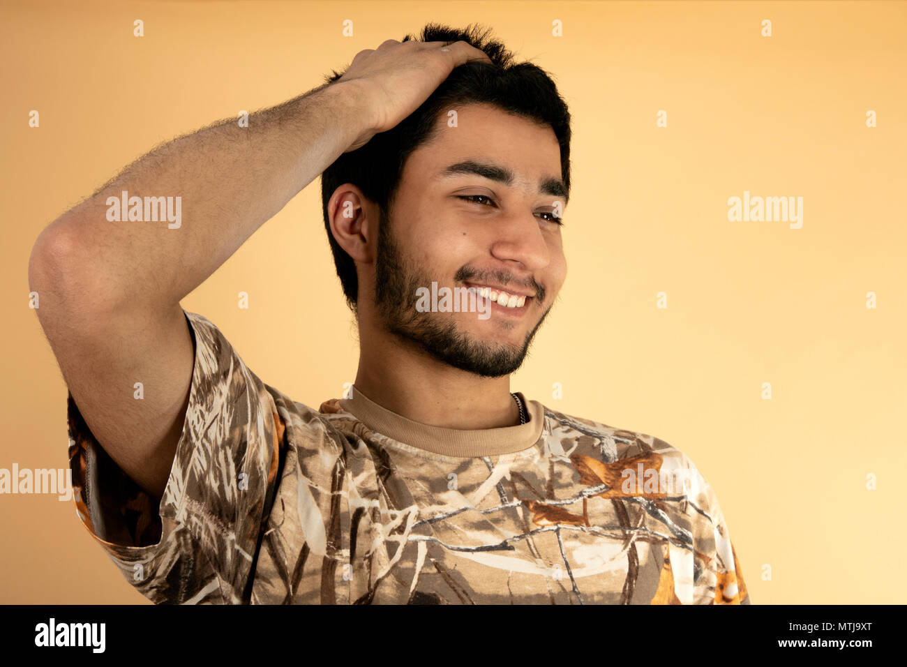 Young man with hand in his hair on beige Background Stock Photo
