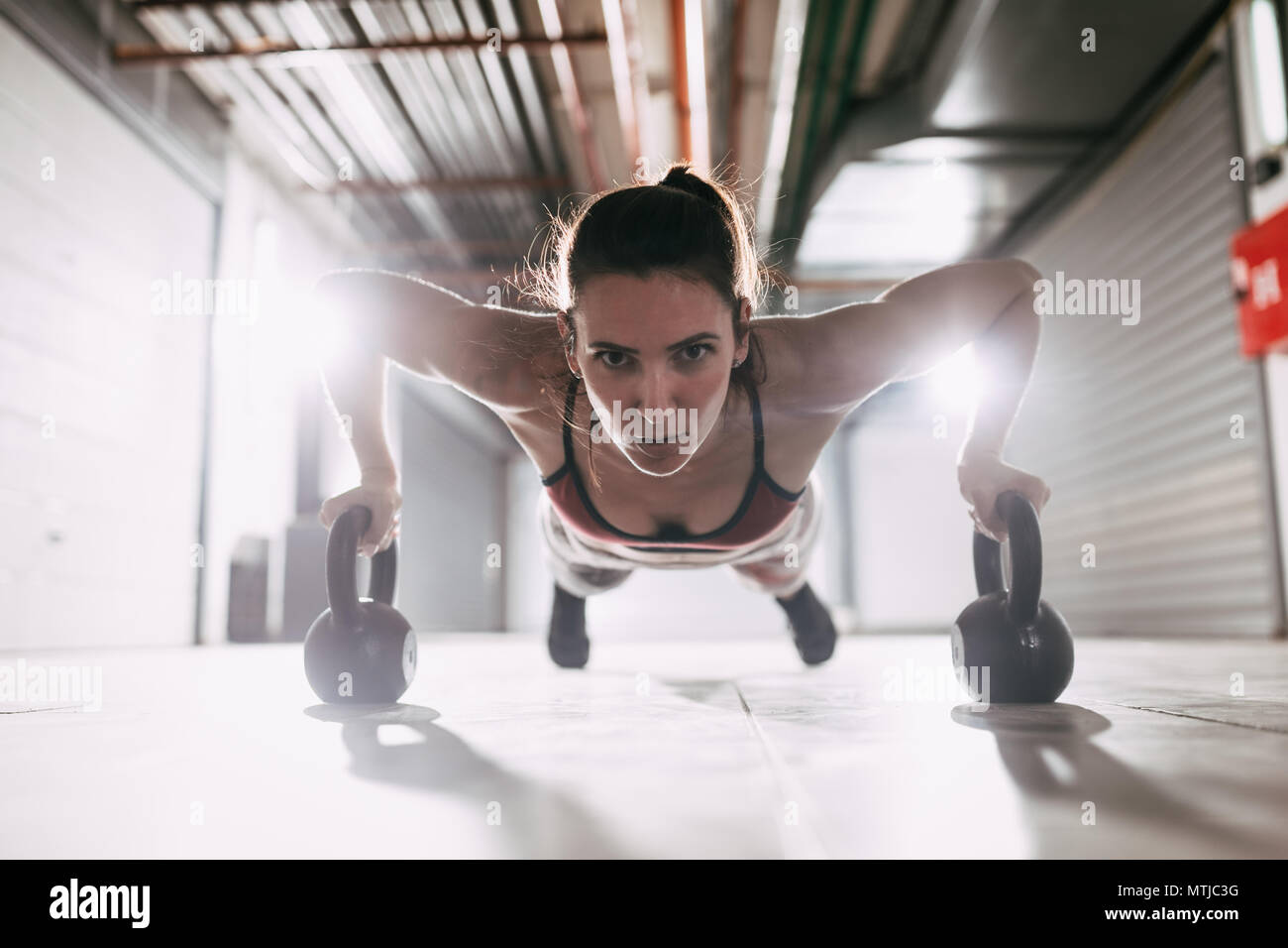 Young muscular woman doing push up exercise on a kettlebells at