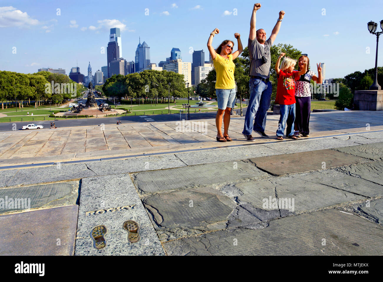 Family posing next to the footprints of Sylvester Stallone at the Rocky Steps - made famous in the movie Rocky Balboa, Philadelphia, Pennsylvania, USA - Stock Image