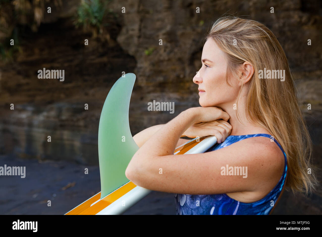 Sporty girl in bikini with surfboard stand by black cliff on beach. Surfer woman look at sea surf and breaking waves. Active people in sport adventure - Stock Image