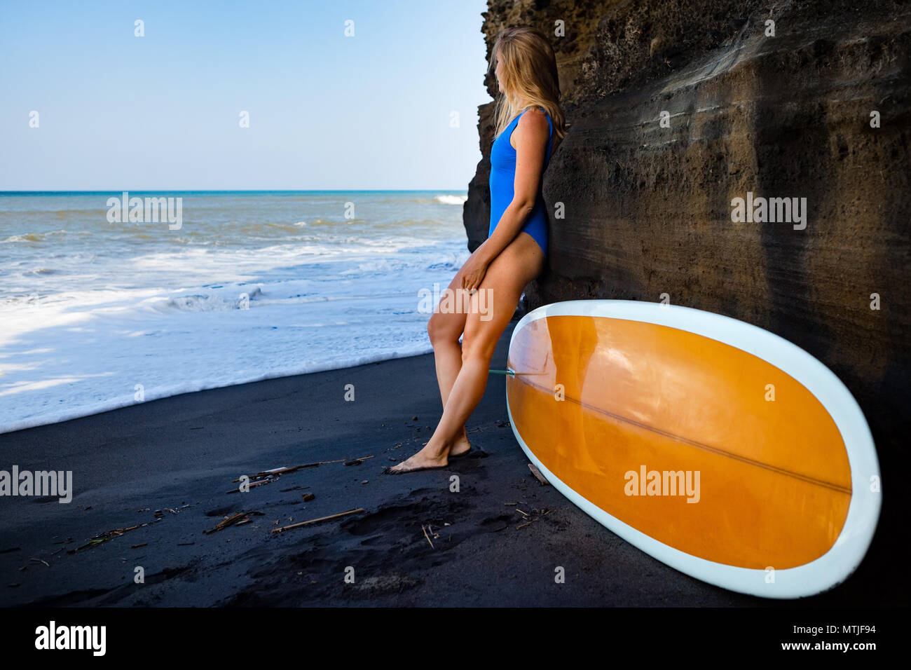Girl in bikini with surfboard stand by cliff on black sand beach. Surfer woman look at sea surf and breaking waves. Active people in sport adventure - Stock Image