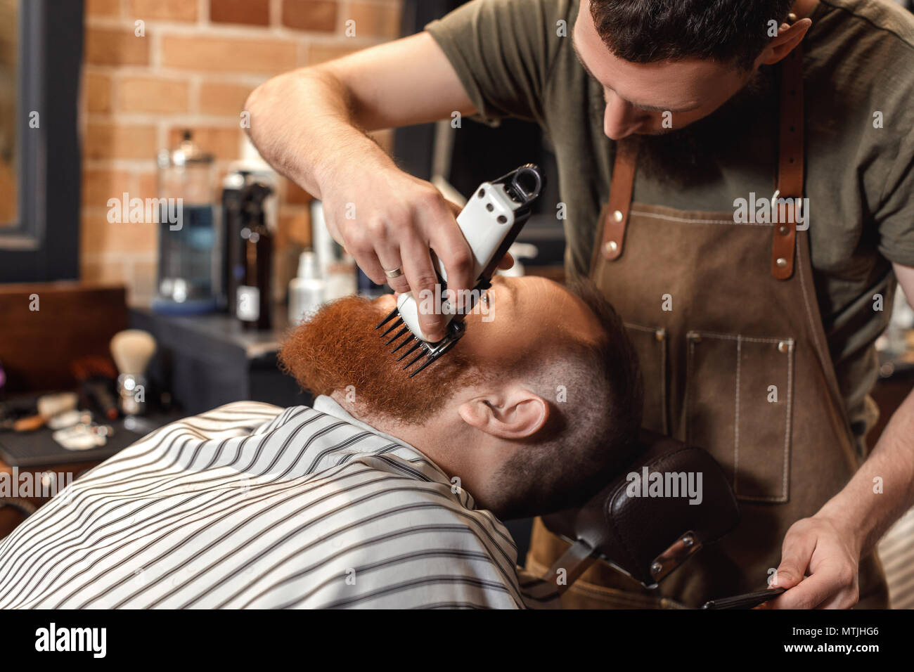 Barber and bearded man in barber shop - Stock Image