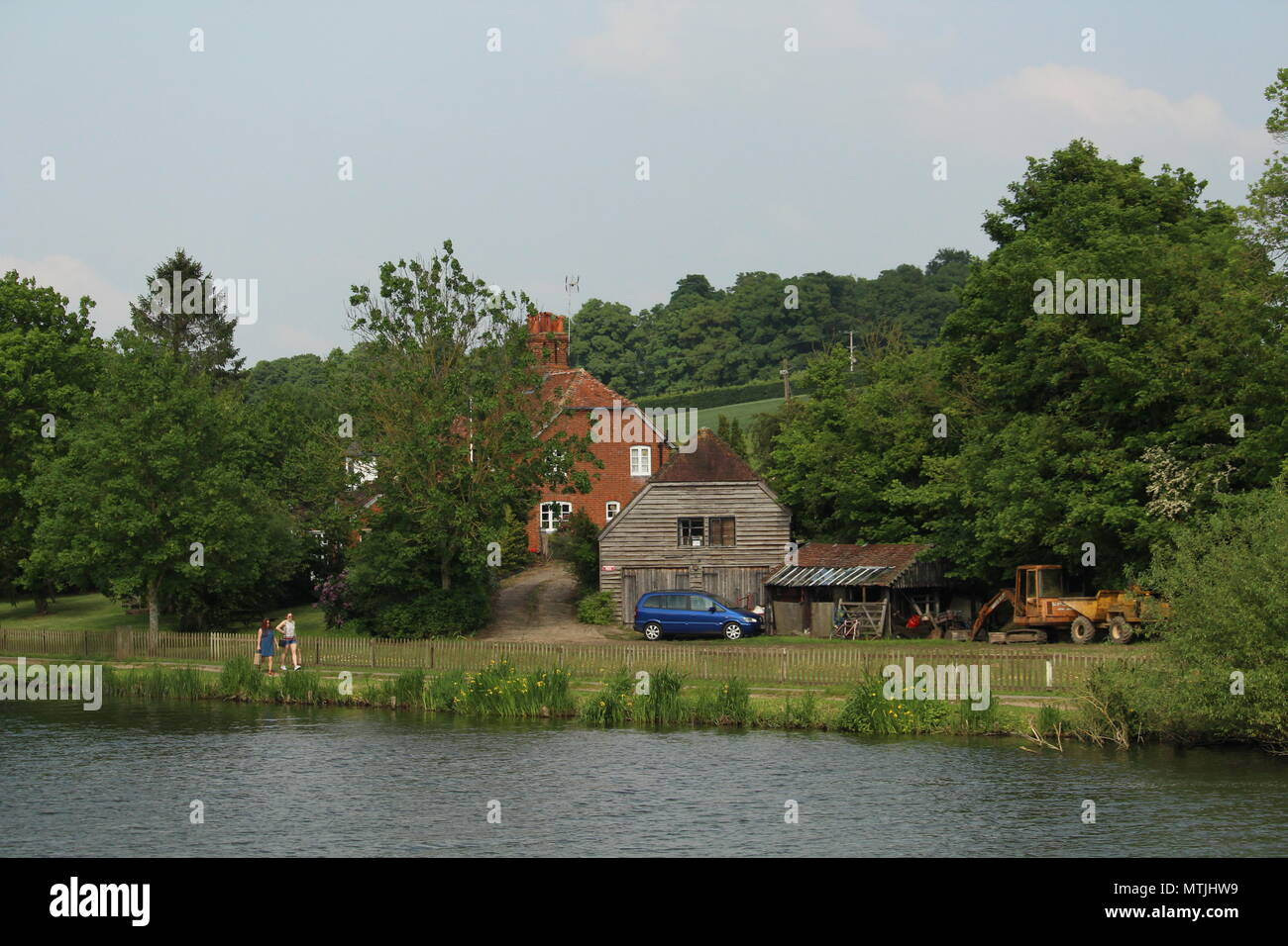 Lifestyle - couple walking  alongside waterfront property on River Thames at Henley-on-Thames Oxfordshire, Britain. - Stock Image