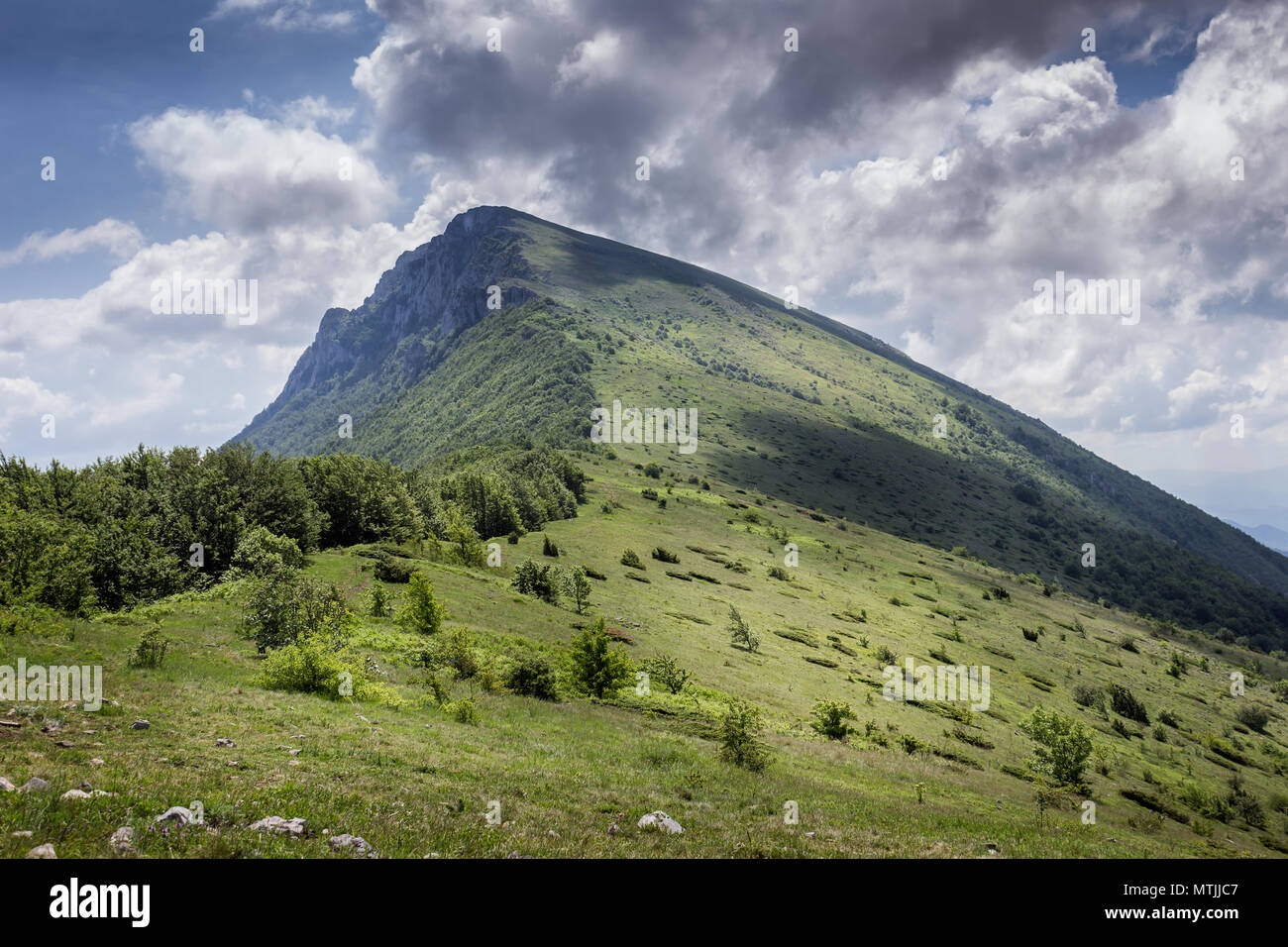 Storm is coming over Trem summit with dramatic clouds dropping shadow on the highlands of Dry mountain in Serbia - Stock Image