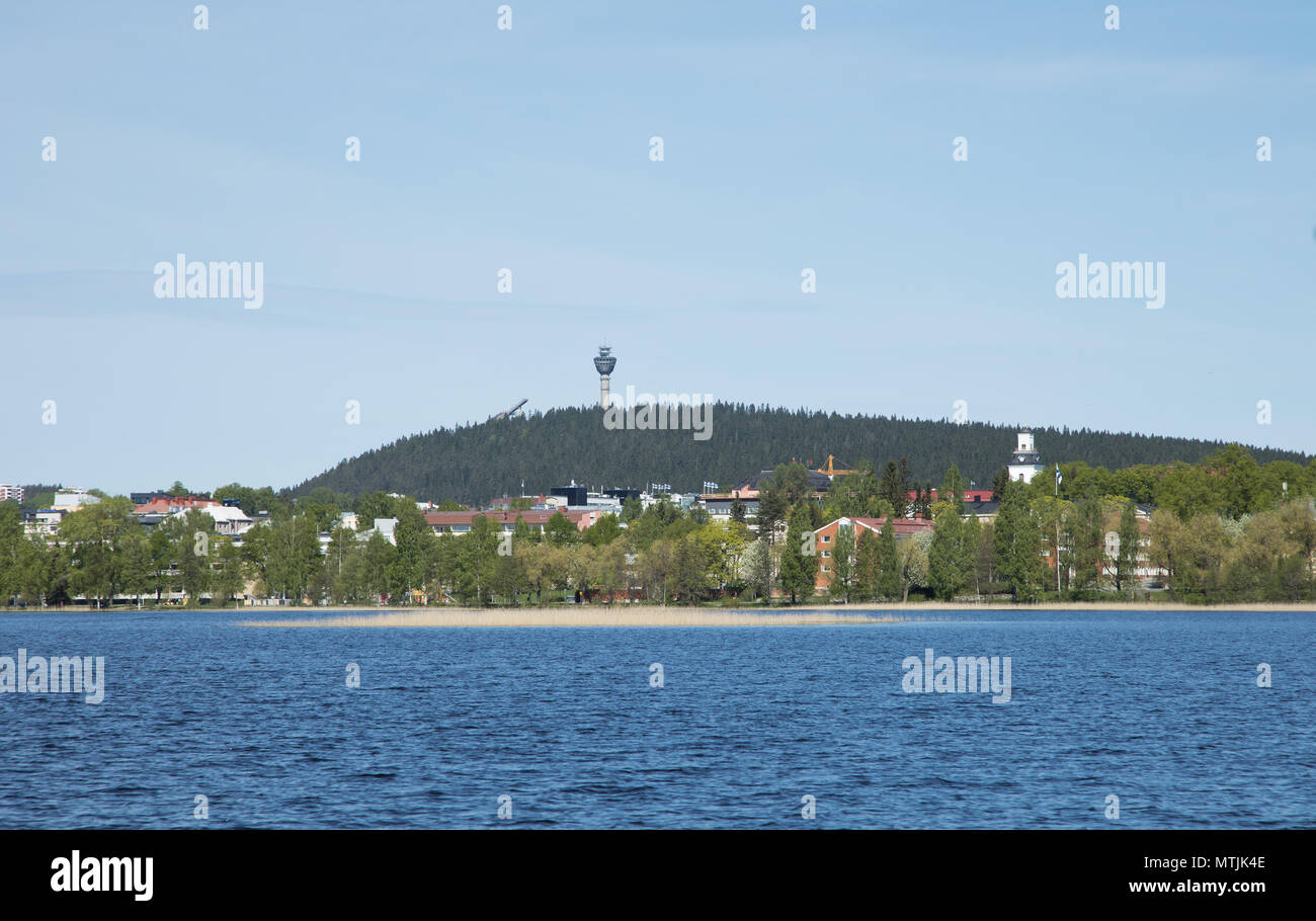 City of Kuopio in Eastern Finland at the shores of Lake Kallavesi, in front of Puijo mountain with its scenery tower and ski-jump tower sticking up. Stock Photo