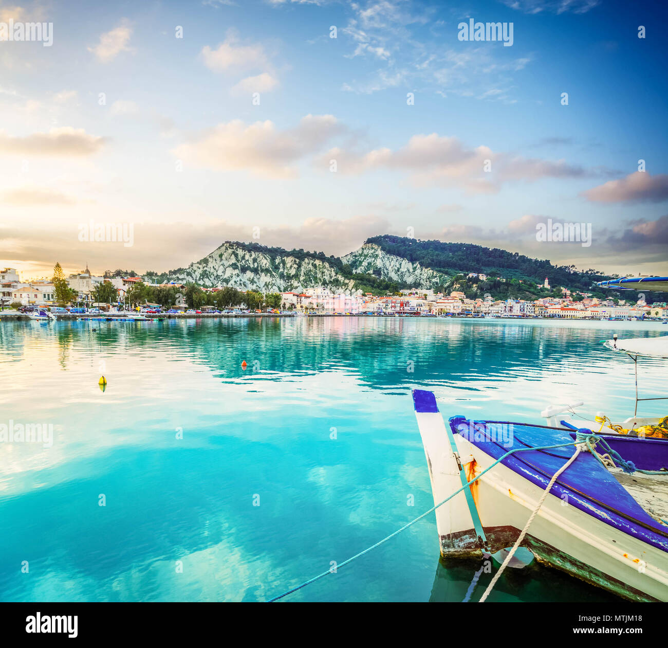 fishing boats in Zaante town harbour under sunset sky, Zakinthos Greece, toned Stock Photo