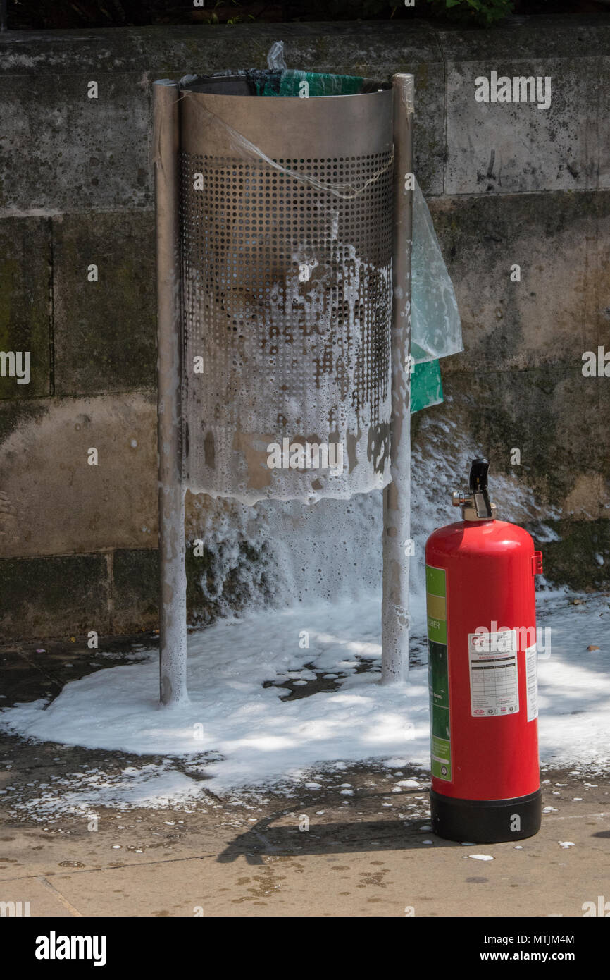 a fire in a waste paper bin or litter bin at the side of the road. extinguisher used to put out a fire in a rubbish bin to prevent it from spreading. - Stock Image