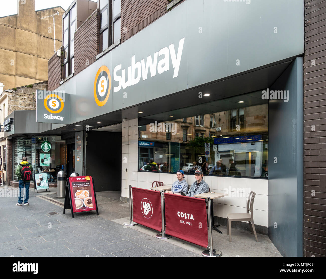 Two young men in the Costa outdoors seating area in front of Hillhead Subway Station in Byres Road, Glasgow; another man looks in through the Starbuck - Stock Image