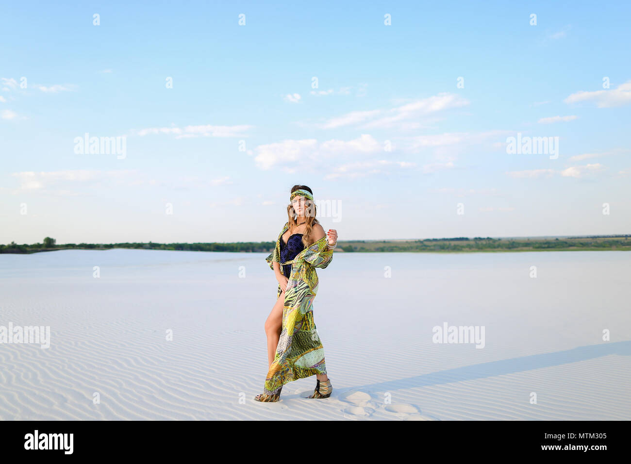 Young female person wearing swimsuit and green beach robe standi - Stock Image