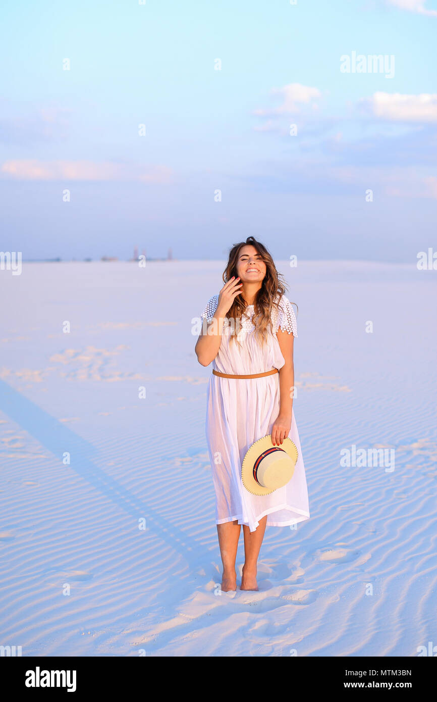 Young european woman keeping hat, wearing dress and standing on  - Stock Image