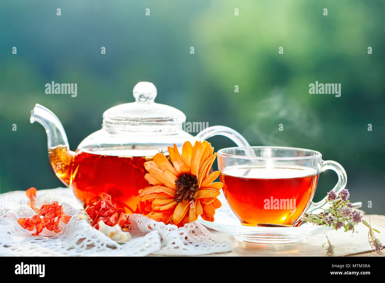 Cup with hot tea with mint and a thyme on a wooden table in a summer garden. Selective focus, Stock Photo
