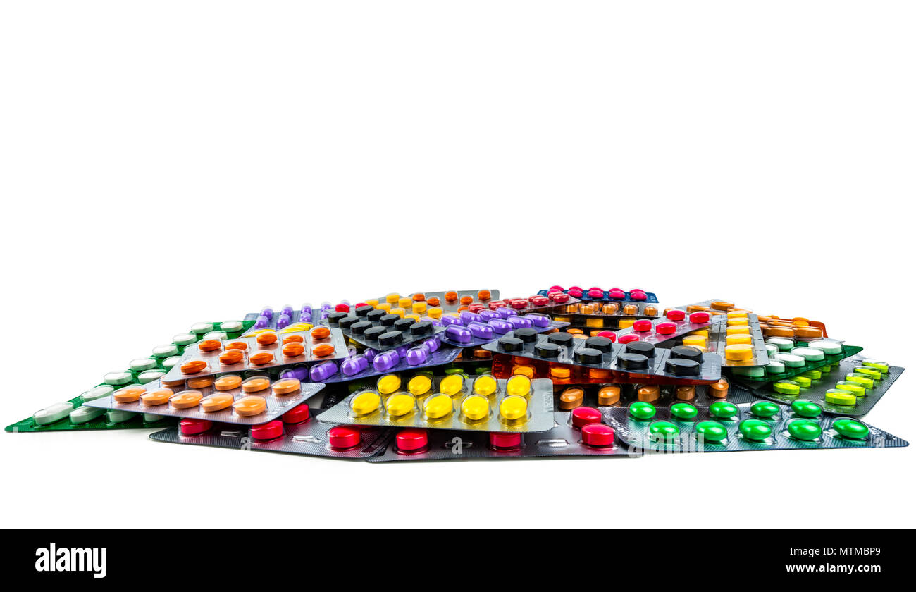 Pile of tablet pills isolated on white background. Yellow, purple, black, orange,  pink , green tablet pills in blister pack. Painkiller medicine. Dru Stock Photo