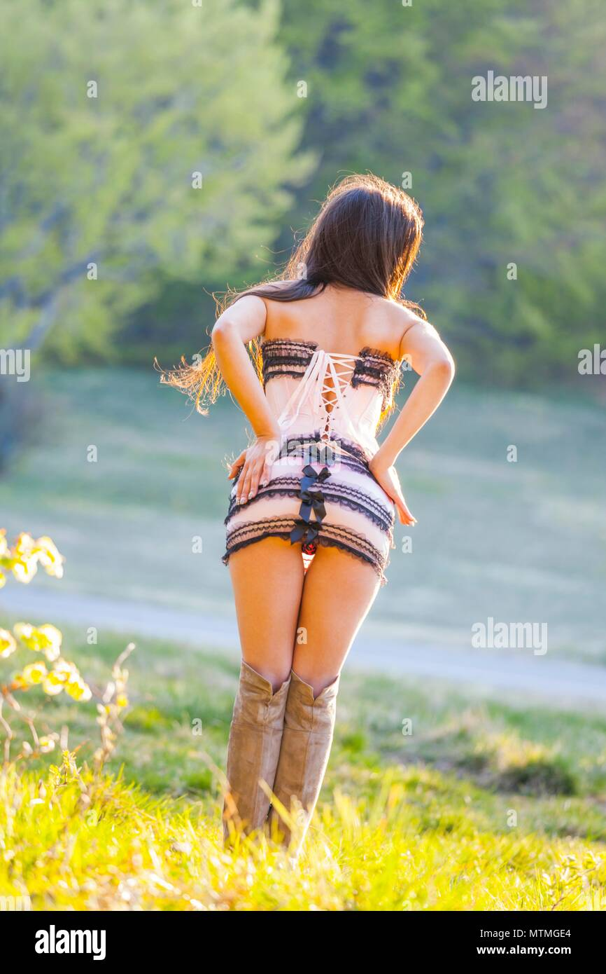 Pretty female teenager view from rear behind back hands on hips - Stock Image