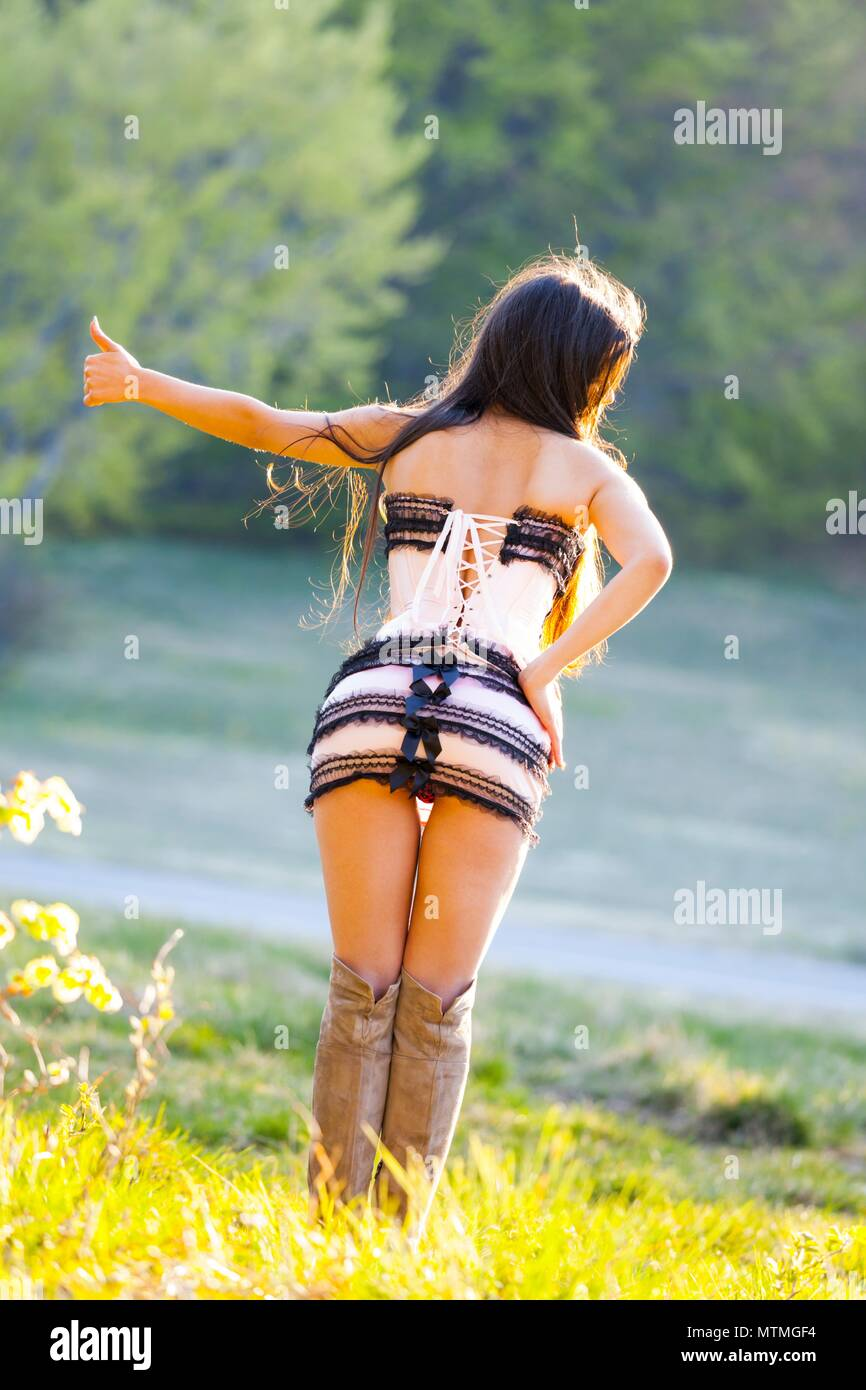 Pretty female teenager view from rear behind back extended finger and hand  hitchhiking on countryside road youngadult young-adult Stock Photo