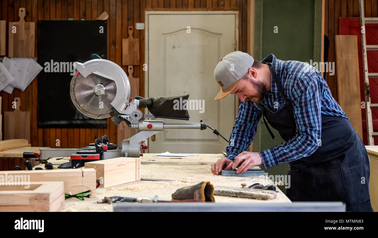 Experienced carpenter in work clothes and small buiness owner working in woodwork workshop, sharpening the tool with whetstone Stock Photo