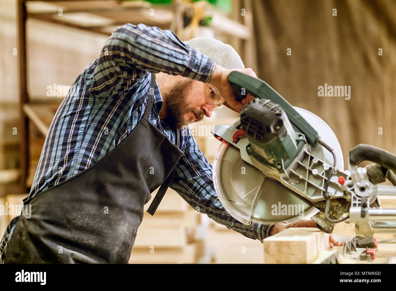 Carpenter work with circular saw for cutting boards, the man sawed bars, construction and home renovation, repair and construction tool - Stock Image
