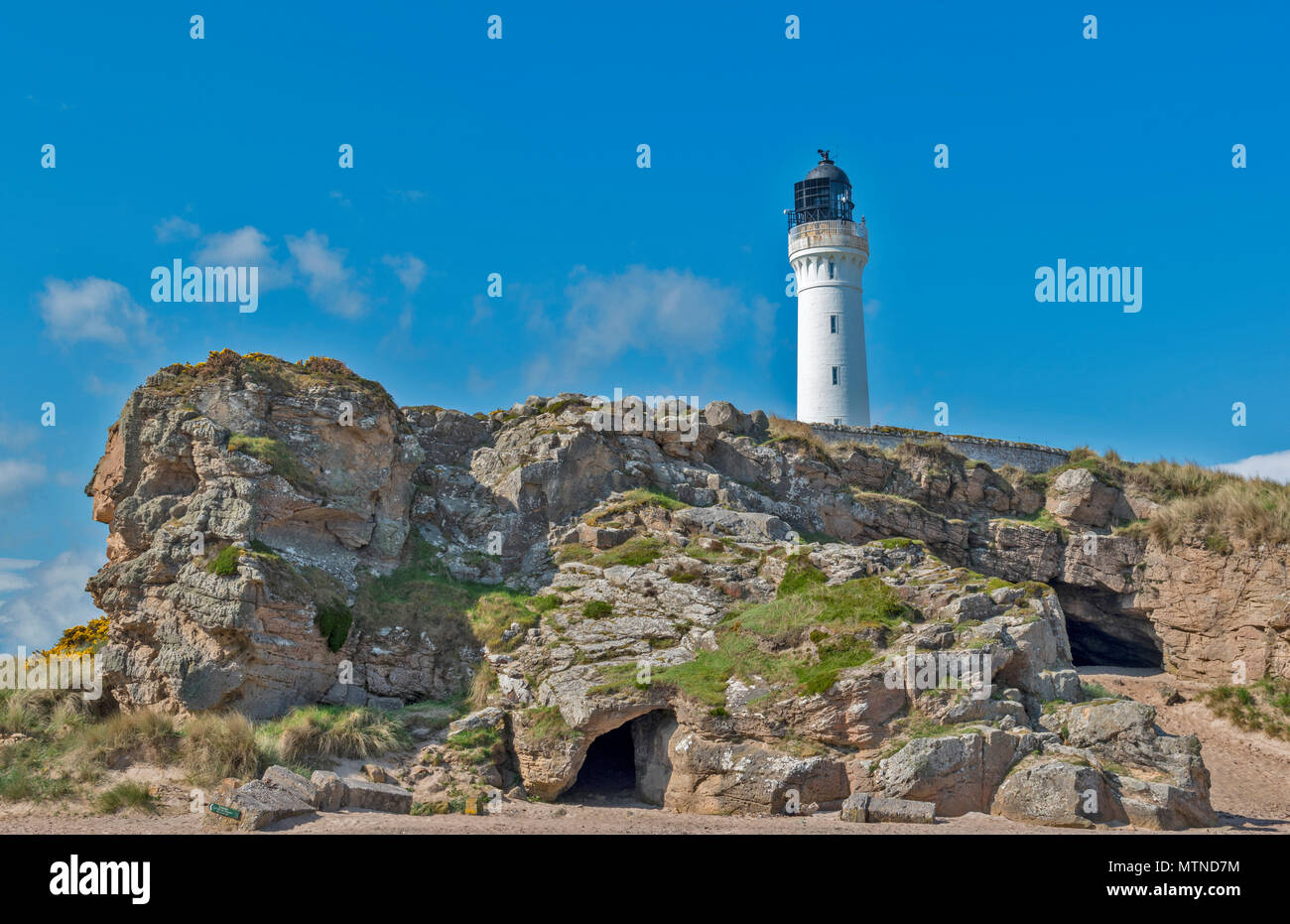 COVESEA LIGHTHOUSE LOSSIEMOUTH BEACH SCOTLAND WHITE COLUMN ON A HILL WITH ROCKS AND CAVES AN EARLY MORNING IN SPRING - Stock Image