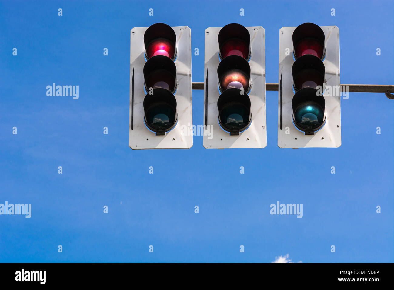 A traffic light and a surveillance camera on a pole mounted on the street. Stock Photo
