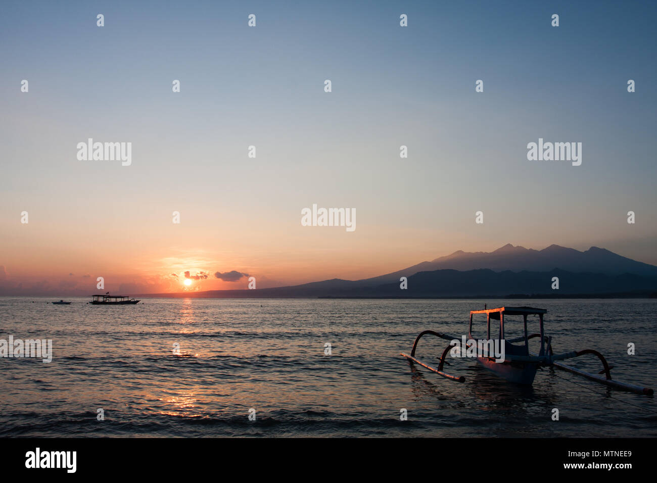Sunrise on the beach at Gili Air. Rinjani volcano in the background. Indonesia. - Stock Image