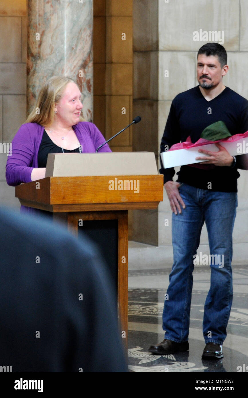 """Gold Star wife Tiffany Bock speaks to a crowd at the State Capitol Building in Lincoln, Nebraska, Jan. 9, during a 'Remembering Our Fallen' ceremony put on by Bill and Evonne Williams of Patriotic Productions, a non-profit organization. Kris """"Tanto"""" Paronto (right) holds flowers presented to Tiffany in honor of her late husband, Marine Staff Sgt. Michael Bock, who was killed in Afghanistan in 2010. - Stock Image"""