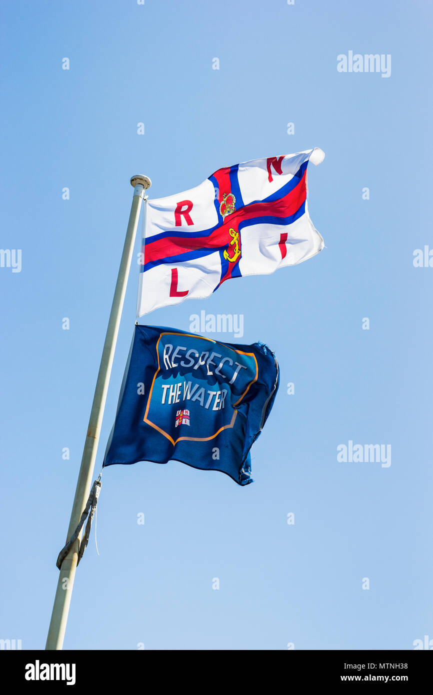 RNLI and respect the water flags against a blue sky with copy space - Stock Image